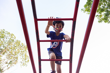 Gabriel, 7, climbs a jungle gym at a local park, in Moreno, Argentina, on Dec. 10, 2020. The family often goes to play in the park so that the children can be outdoors. The CST programme teaches caregivers of children with developmental delays and disabilities the skills to enhance their children's development through play and home routines.  The Caregiver Skills Training (CST) programme was developed by WHO and is being implemented in Argentina by international partner Programa Argentino para Niños, Adolescentes y Adultos con Condiciones del Espectro Autista (PANAACEA) to serve families of children with developmental delays and disabilities. The programme uses a family-oriented approach and is designed to be delivered by trained non-specialists (community-based workers, peer caregivers or others) as part of a network of health and social services for children and their families. CST consists of nine group sessions and three individual home visits, focused on training caregivers how to use everyday play and home activities and routines as opportunities for learning and development. The sessions specifically address communication, engagement, daily living skills, challenging behaviour and caregiver coping strategies.   Gabriel was diagnosed with autism at age 3. He was not speaking and did not interact with other people, including his family. As a mother of four, Karina Visciglia struggled to care for her family and find Gabriel the services he needed. Through CST facilitators and PANAACEA, Karina gained access to a network of services and a support system. She saw significant improvements in her ability to connect and communicate with her son, and did so through the use of play activities, games, and home routines. She also says she felt empowered and improved herself by taking part in the group sessions.  In general, caregivers of children with developmental delays often experience very high levels of distress and, in many cases, interruptions or discontinuation of