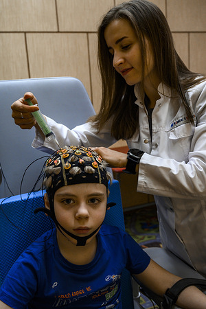 """Patient with a therapist during a """"Exo-wrist"""" session (neural interface brain-computer) at Russian Children's Clinical Hospital in Moscow.  Diagnosis: Cerebral palsy, left hemiparesis (intraventricular bleed grade 3-4 at gestation age week 32). Diagnosed when 1 yeal old."""