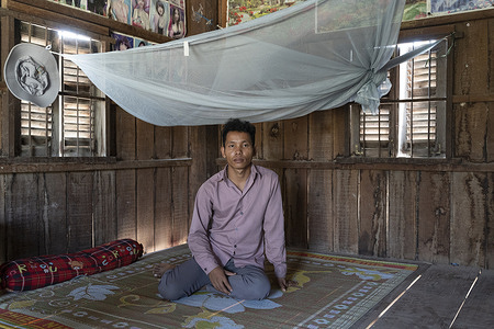 """Thong Yim, 26, a recovered malaria patient, sits under a mosquito net in his house in Peam L'vear village in Cambodia on 29 January 2021. In 2020, men constituted 81% of all malaria cases in Cambodia.   Kampong Speu province is located in one of Cambodia's malaria hotspots. Malaria work in the province can be challenging due to high levels of multidrug resistance and the remaining infections predominantly coming from remote forested areas. Cambodia has been the infamous epicentre of resistance to various artemisinin-based combined therapies (ACTs) –the most effective treatment for malaria. In 2017, Cambodia's National Center for Parasitology, Entomology and Malaria Control (CNM) launched a malaria intensification to deplete parasite reservoirs in high-risk populations by deploying technical support to provinces, strengthening coordination, and ensuring the full implementation of malaria interventions. Since then, Cambodia has reached historically low malaria incidence levels. In November 2020 the CNM launched the last stage of its intensification plan, a focalized aggressive approach to eliminate P. falciparum malaria by 2023. In Cambodia, this approach is known as the """"last mile"""" of malaria elimination. The response is part of a broader initiative supported by WHO's Mekong Malaria Elimination programme to eliminate malaria in the Greater Mekong subregion by 2030."""