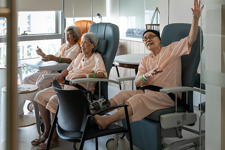 """Patients (L-R) Khoo Kim Chai, Chua Cheng Leong and Cheng Wang Moy enjoy a virtual performance during Variety Hour in their ward in Outram Community Hospital in Singapore, 4 March 2021. The population in Singapore and the Western Pacific Region is ageing rapidly. In order to prepare, society and healthcare systems are evolving to support people throughout their life with long-term care and social services integrated at the community level. As Singapore's only cluster of community hospitals, SingHealth Community Hospitals (SCH) supports the nation's ageing population by establishing partnerships between community welfare services and its own community health team, including nurses, doctors and allied health staff.    To that end, this social prescription (prescribing community involvement vs. drugs) aims to go beyond the health sector to address the underlying social factors in treating a person. SCH aims to address social determinants of health early in the inpatient setting through social prescribing, particularly when its patients stay for an average length of 21 days, and with about 90% of them above 60 years old.   The goal of social prescribing is to connect the health and social sectors to provide more holistic care to patients through addressing the social determinants of health and underlying psychosocial factors that contribute to poor health. This approach takes various forms, such as healthcare providers directly referring patients to community-based services, or referring them to specialized in-house """"link workers"""" or what is referred to by SingHealth as wellbeing coordinators, who provide referred patients with focused counselling. Wellbeing coordinators can also co-design personalized wellness plans with patients, routinely follow up on patients to monitor their progress, and make use of behaviour change techniques. During COVID-19, this programme has also helped teach older people how to use smartphones, QR codes, Wi-Fi and WhatsApp in order to stay co"""
