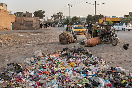 On 25 March 2021 trash and waste are both discarded and collected by the road in Heart, Afghanistan.