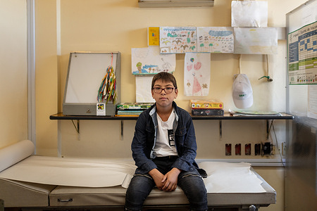 """Tuesday, February 23, 2021, Montevideo, Uruguay. Unidad Pediátrica Ambiental.Lautaro Acosta Salinas, 10, at the doctor's office at Unidad Pediátrica Ambiental. Lautaro was sent to UPA when he was 8 years old, because of high levels of lead in his bloodstream.   Lautaro's family ran a business which bought and sold different kinds of metals. Lautaro had a habit of putting these metals in his mouth. At school he started having trouble concentrating and started to be anxious and aggressive. The doctors at UPA have been following Lautaro for about 3 years and monitoring the lead levels in his blood. - In Uruguay's low-income neighborhoods, it is common for people to burn cables, discarded electronic equipment, batteries or other e-waste to recover metals for profit. In some settlements, large spots of burned lead can be seen on the street. Other contaminants include mercury and dioxides. While these """"urban mining"""" activities are illegal, it is how many people make their living. E-waste is a health and environmental hazard, containing toxic additives or hazardous substances which damage the human brain, among other systems. The WHO Initiative on E-waste and Child Health was launched in 2013. With 25% of children in Uruguay now showing high levels of lead in their blood, one of the top priorities is protecting children from lead poisoning.  Young children are particularly vulnerable to lead exposure as they absorb four to five times as much ingested lead as adults from a given source. Health consequences are serious as at high levels of exposure, lead poisoning attacks the brain and central nervous system, causing coma, convulsions, intellectual disabilities and even death. At lower levels of exposure, lead can affect a child's brain development, resulting in reduced intelligence quotient and diminished educational attainment. Unidad Pediátrica Ambiental (UPA) is a national pediatric centre that specializes in environmental health and is connected to WHO's Children's Envi"""