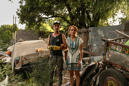 """Portrait of Maria Carballo and Luis Zapata, standing in the front of their home a settlement located across from the main garbage dump in Montevideo, Uruguay, on 1 March 2021. - In Uruguay's low-income neighborhoods, it is common for people to burn cables, discarded electronic equipment, batteries or other e-waste to recover metals for profit. In some settlements, large spots of burned lead can be seen on the street. Other contaminants include mercury and dioxides. While these """"urban mining"""" activities are illegal, it is how many people make their living. E-waste is a health and environmental hazard, containing toxic additives or hazardous substances which damage the human brain, among other systems. The WHO Initiative on E-waste and Child Health was launched in 2013. With 25% of children in Uruguay now showing high levels of lead in their blood, one of the top priorities is protecting children from lead poisoning.  Young children are particularly vulnerable to lead exposure as they absorb four to five times as much ingested lead as adults from a given source. Health consequences are serious as at high levels of exposure, lead poisoning attacks the brain and central nervous system, causing coma, convulsions, intellectual disabilities and even death. At lower levels of exposure, lead can affect a child's brain development, resulting in reduced intelligence quotient and diminished educational attainment. Unidad Pediátrica Ambiental (UPA) is a national pediatric centre that specializes in environmental health and is connected to WHO's Children's Environmental Health programme. The centre is part of the toxicology department in the School of Medicine of the Universidad de la República, located inside the Claveaux centre of Health in Montevideo, Uruguay. UPA aims to prevent diseases that are generated by environmental contaminants, especially in children. Doctors at UPA treat children, adolescents, and pregnant women. UPA is also an education facility where both graduate"""