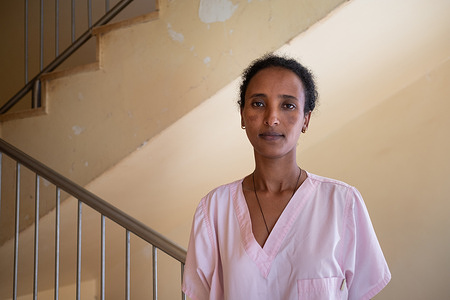 Yewognesh Gebre-Meskel stands for a portrait at Felege Hiwot Hospital in Bahir Dar, Ethiopia on 25 March 2021. Yewognesh works as a nurse at the hospital's KMC unit.  Kangaroo mother care (KMC) is an effective way to prevent mortality in both preterm and low birth weight (LBW) infants. KMC is prolonged skin-to-skin contact for the baby with the mother or other caregiver for as long as possible during day and night, as well as exclusive breastfeeding or breast milk feeding. Fathers and other caregivers can also provide skin to skin care.   Among infants born preterm or LBW, KMC has been shown to reduce infant deaths by as much as 40%, hypothermia by more than 70%, and severe infections by 65%. Mothers remain with their babies from birth to be able to breastfeed and practice skin-to-skin contact as part of KMC.  KMC is one of the most cost-effective ways to increase survival of LBW and preterm newborns in low-income countries like Ethiopia. KMC was first introduced in Ethiopia in 1996 at the Black Lion Hospital. Since then, with support from WHO, KMC services have been expanded to other hospitals and health facilities including the Felege Hiwot Hospital, in Bahir Dar.  Globally, with 15 million babies born preterm (before 37 weeks) and 21 million born LBW (under 2.5kg) each year, these infants face significant health risks, as preterm-related complications are the leading causes of death of newborns. Hence, WHO advises that KMC should continue amid the COVID-19 pandemic. This is due to the proven critical importance of ensuring newborns have close contact with parents after birth, especially for those born LBW or preterm.