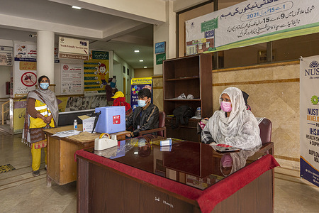 A view of the reception area at Family Health Hospital in Lahore, Pakistan, on 1 February 2021. Sameena Manzur (right) checks temperatures of people who enter the facility as a COVID-19 preventative measure. On the left Gulnaz and Muhammad Bilal wait to vaccinate children against polio.